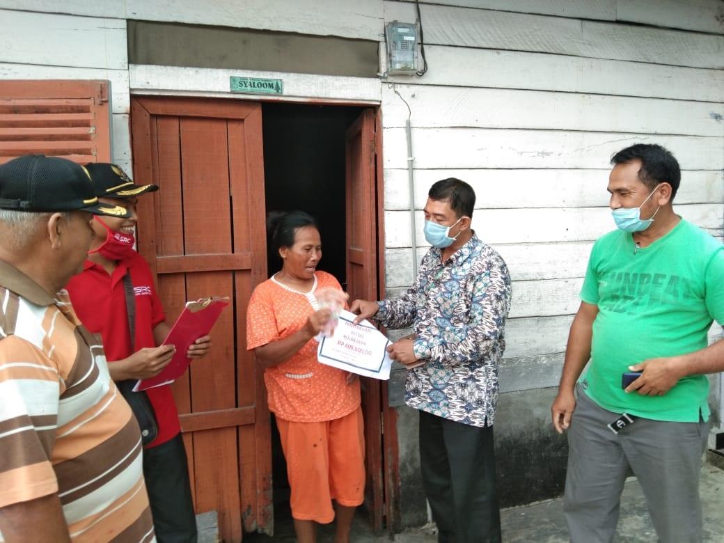 Kepala Desa Serdang, Meranti, Asahan memberikan bantuan untuk warga