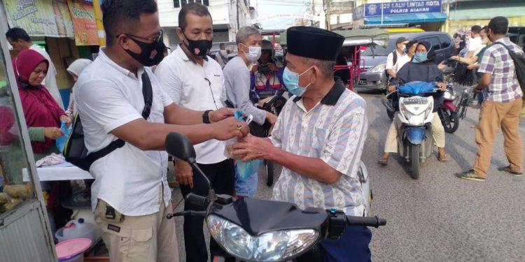 Kanit Reskrim Polsek Kota Kisaran, Iptu Marzuki SH membagikan takjil kepada warga yang melintas.