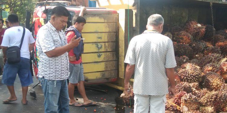 Supir truk bermuatan buah sawit (TDS) Nopol BM 9910 EU mengalami pecah ban dan terguling, Safii (baju merah).