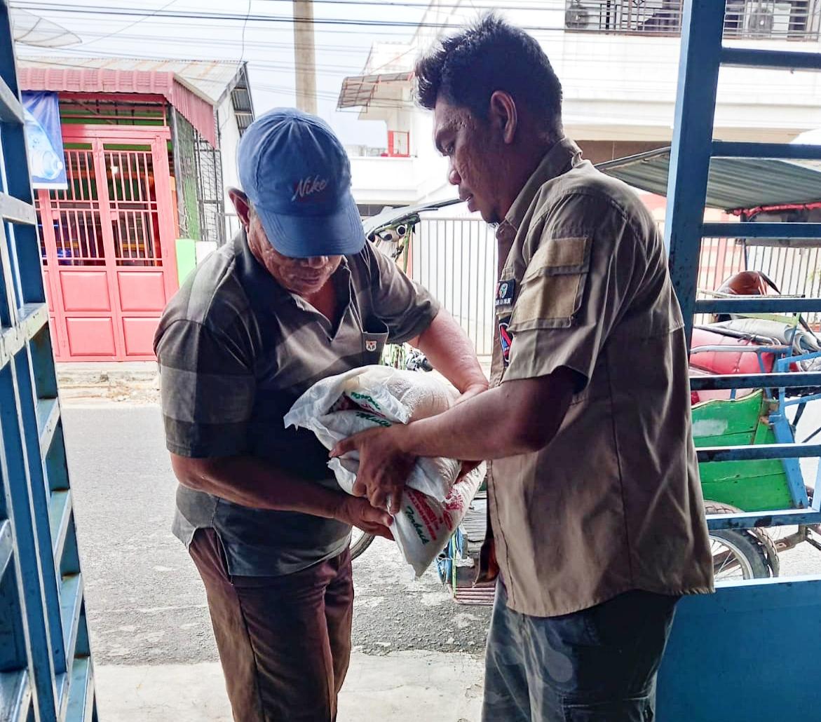 Sekretaris PD IWO Asahan-BatubaraKhairul Anhar Harahap SH saat menyalurkan bantuan beras pada warga